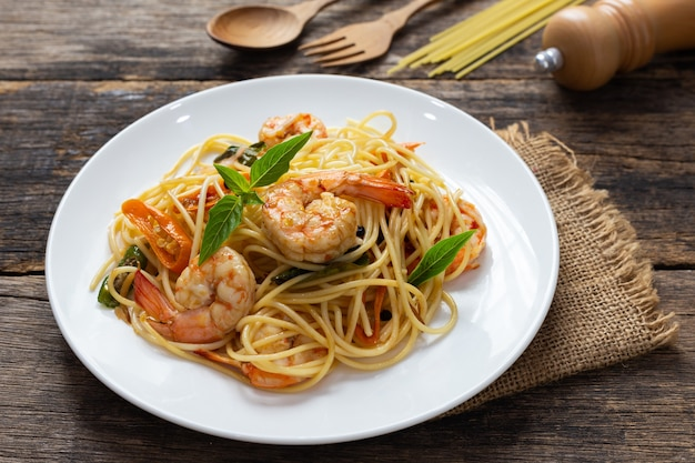 Spaghetti with spicy fried shrimp on a wooden table