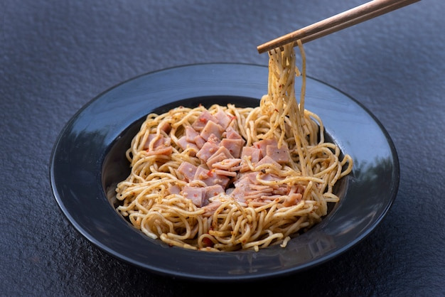 Spaghetti with spicy mixed ham on black plate