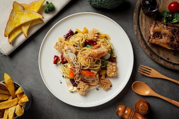 Spaghetti con frutti di mare misti piccanti su fondo scuro