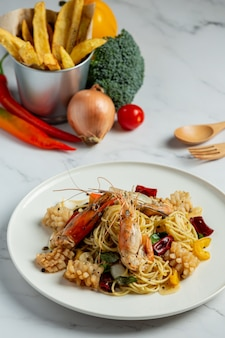 Spaghetti with spicy mixed seafood on marble background