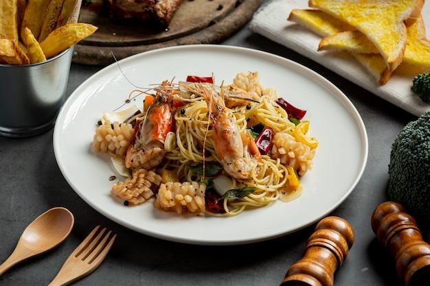 Спагетти с пряными смешанными морепродуктами на темном фоне