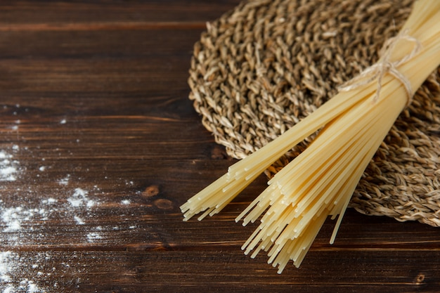 Spaghetti with sprinkled flour on wooden and wicker placemat background, high angle view.