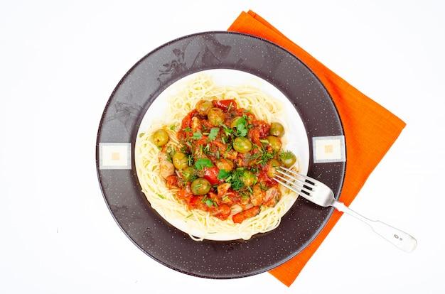 Спагетти с тушеными овощами и зелеными оливками. студийное фото.