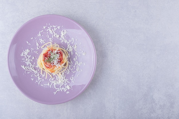 Spaghetti with tomato pasta on purple plate.