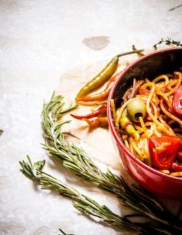 Спагетти с томатной пастой, зеленью и перцем. на деревенском фоне.