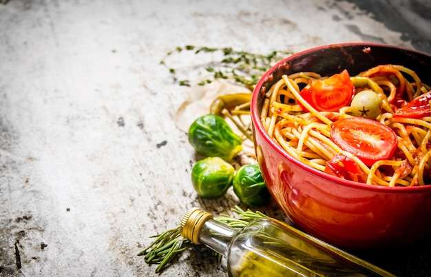 Спагетти с томатной пастой, зеленью и перцем. на деревенском столе. свободное место для текста.