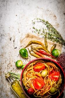 토마토 페이스트, 허브, 후추를 곁들인 스파게티. 소박한 테이블에. 평면도