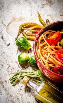 Спагетти с томатной пастой, зеленью и перцем. на деревенском столе.