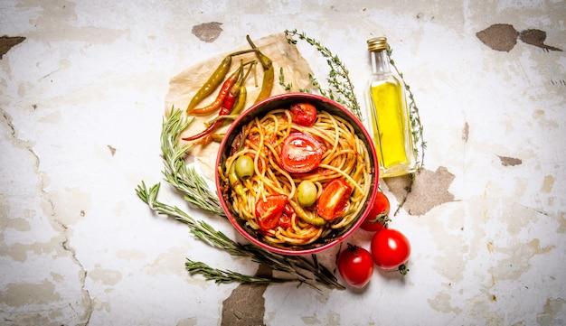 トマトペースト、唐辛子、オリーブオイルのスパゲッティ。素朴な背景に。上面図