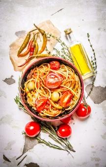 Спагетти с томатной пастой, острым перцем чили и оливковым маслом на деревенском фоне