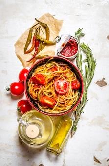 トマトペースト、唐辛子、オリーブオイルのスパゲッティ。素朴な表面に。上面図