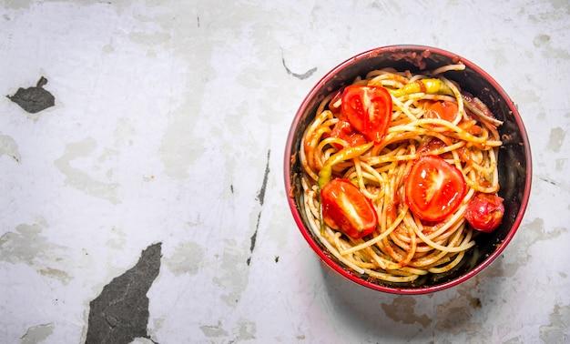 Спагетти с томатной пастой, специями и помидорами в миске.
