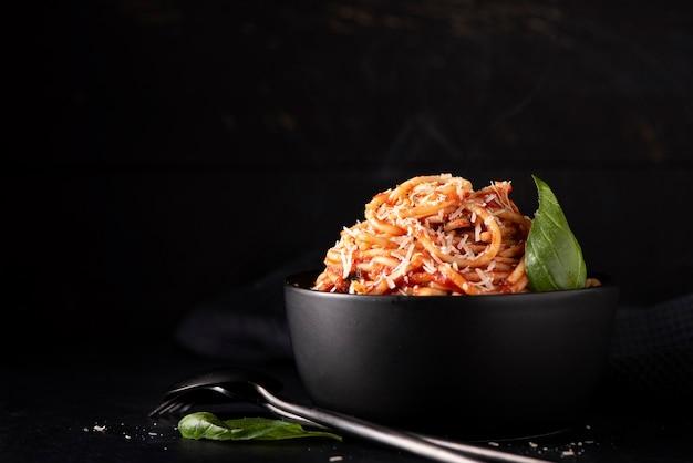 Спагетти с томатным соусом и пармезаном в черной миске