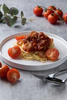 Спагетти с томатным соусом и колбасой в белой тарелке