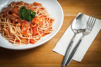 Spaghetti with tomato sauce bacon and cheese with basil leaves and fork and spoon