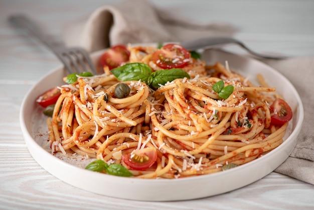 白いプレートにトマトソース、バジル、パルメザンチーズのスパゲッティ