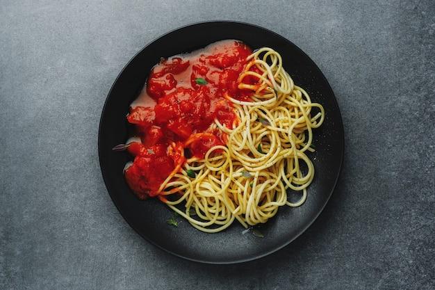 暗いテーブルの暗いプレートにトマトソースのスパゲッティ。上面図。