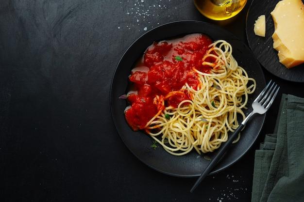 어두운 테이블에 어두운 접시에 토마토 소스 스파게티. 평면도.