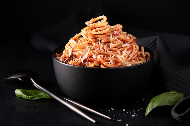 Spaghetti with tomato sauce and parmesan in black bowl