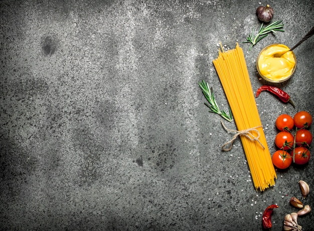 素朴な背景にトマト、マスタードソース、スパイスのスパゲッティ