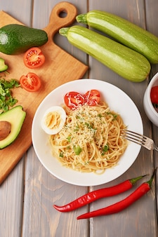 Spaghetti with vegetables, avocado, sweet peppers, cherry tomatoes and parmesan cheese as part of the dish.