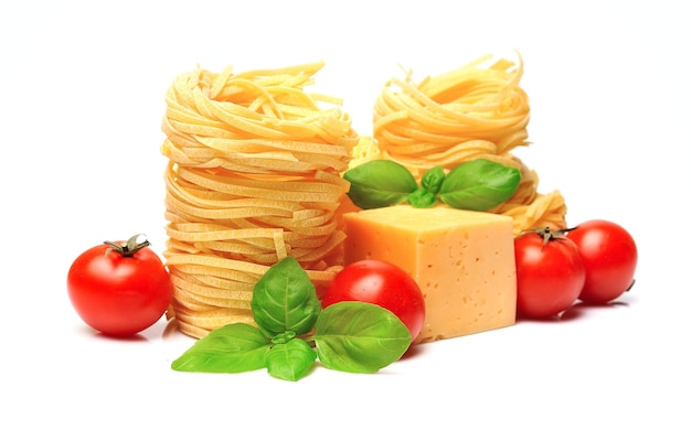 Spaghetti with vegetables and basil on white