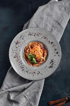 野菜のトマトソースと肉のスパゲッティ。伝統的なイタリア料理。食べ物の写真。シェフからの料理。美しいフィード、クローズアップショット、上面図、コピースペース。 Premium写真