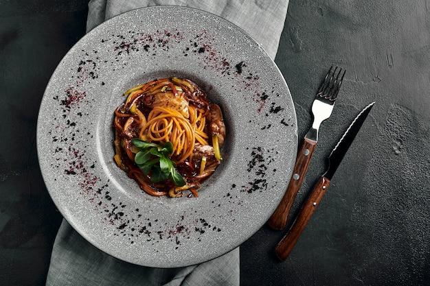 野菜のトマトソースと肉のスパゲッティ。伝統的なイタリア料理。食べ物の写真。シェフからの料理。美しいプレゼンテーション、マクロ撮影、クローズアップ、上面図。