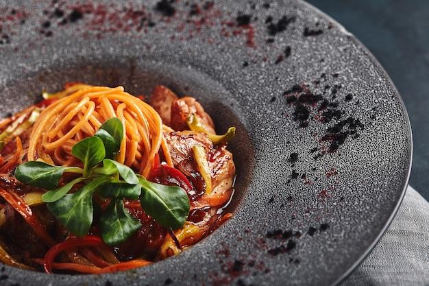 野菜のトマトソースと肉のスパゲッティ。伝統的なイタリア料理。食べ物の写真。シェフからの料理。美しいプレゼンテーション、マクロ撮影、クローズアップ。