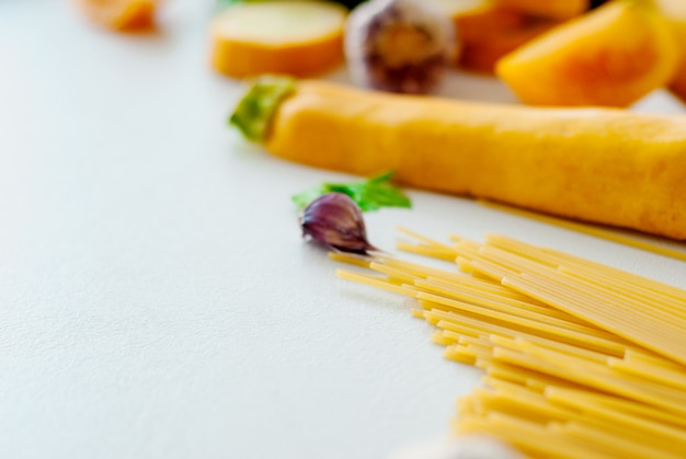 Spaghetti with yellow zucchini, tomato, garlic, champignon, parsley on white background flat lay