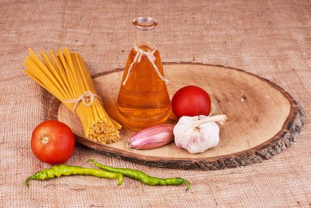 Spaghetti su una tavola di legno con ingredienti.