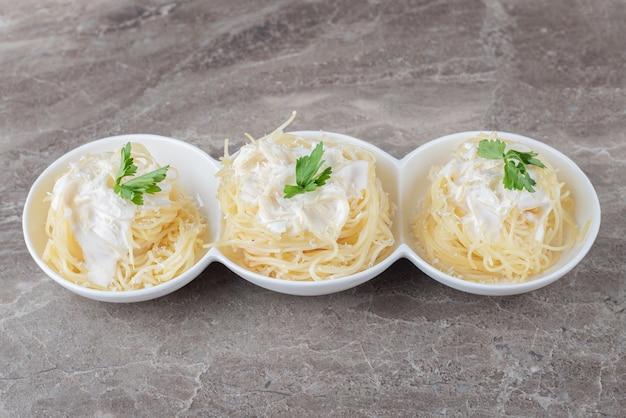 Спагетти, йогурт и зеленые овощи на тарелке, на мраморной поверхности.
