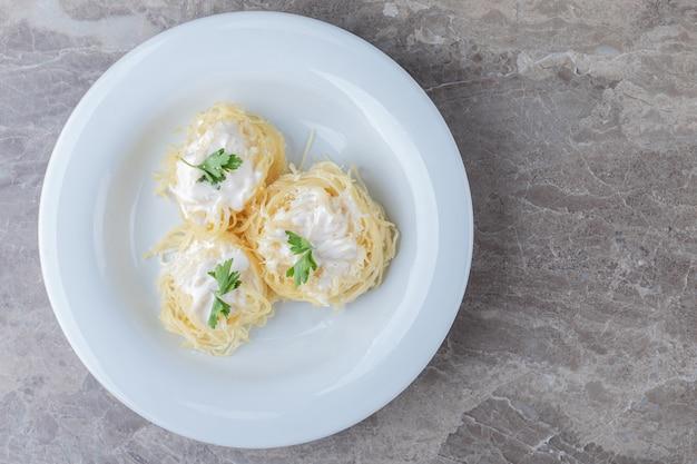 Спагетти, йогурт и зеленые овощи на тарелке, на мраморе.