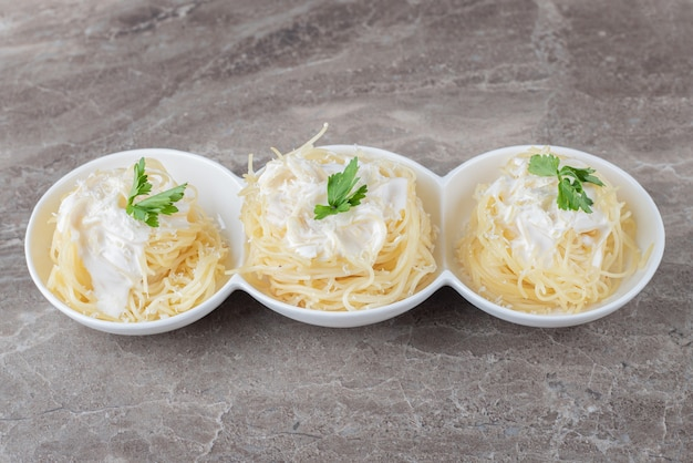 Spaghetti, yogurt e verdura verde sulla piastra, sulla superficie di marmo.