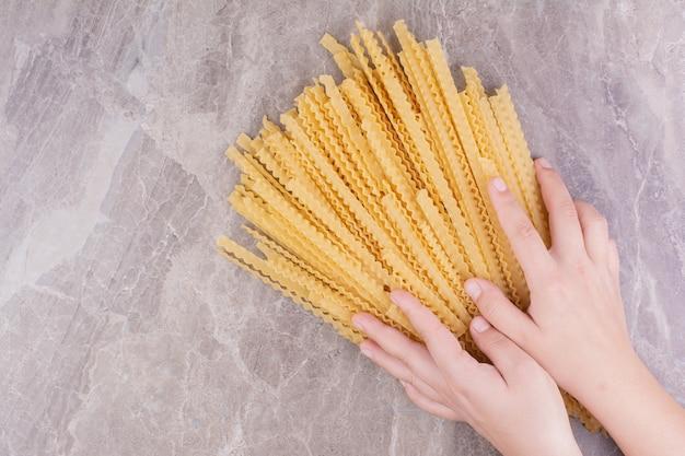 Пучок спагетти, изолированные на мраморном пространстве.