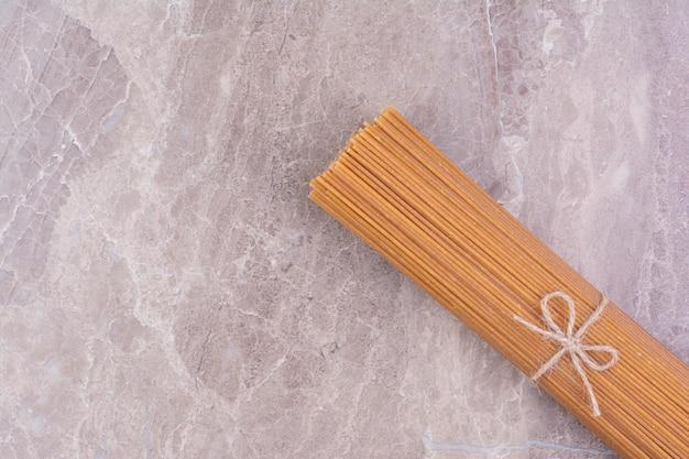 Spaghetti isolati su superficie di marmo grigio