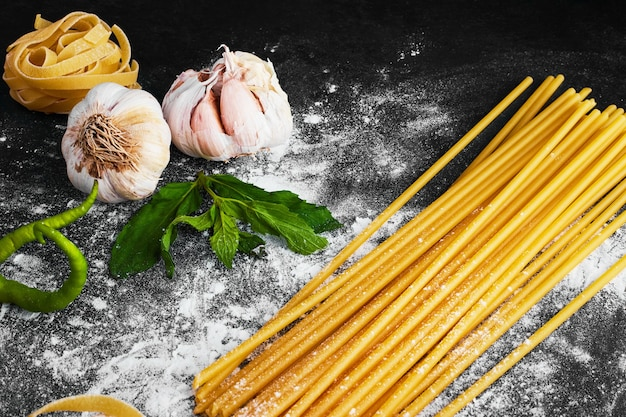 Спагетти на черном с чесноком вокруг.