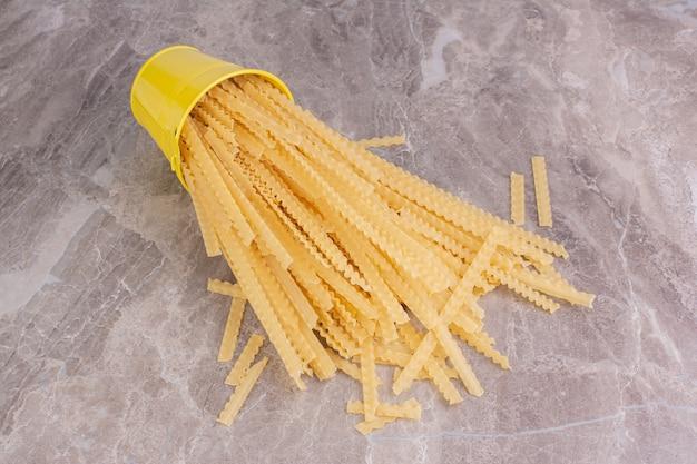 黄色の金属製のバケツから出たスパゲッティ。