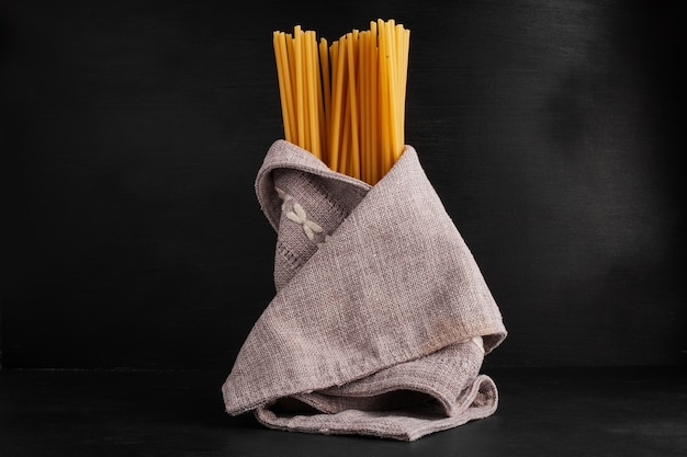 Spaghetties wrapped with a kitchen towel.