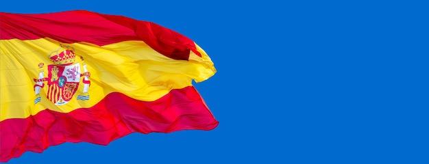 Флаг испании на ветру на фоне голубого неба