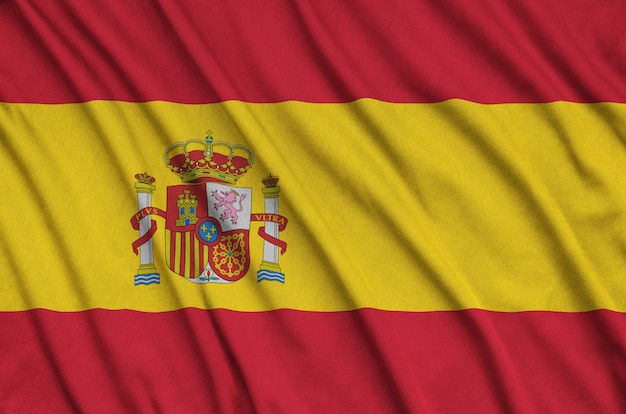 Spain flag is depicted on a sports cloth fabric with many folds.