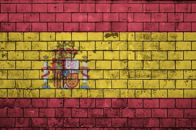 Spain flag is painted onto an old brick wall