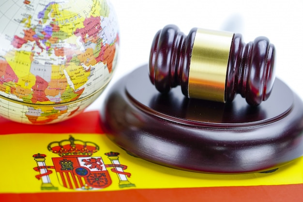 Spain flag and judge hammer with globe world map. law and justice court concept.