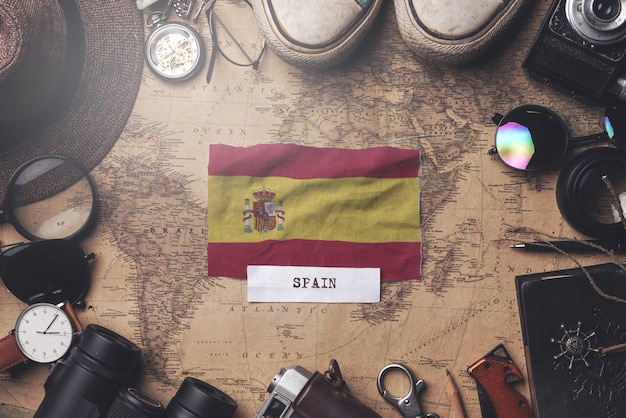 Spain flag between traveler's accessories on old vintage map. overhead shot