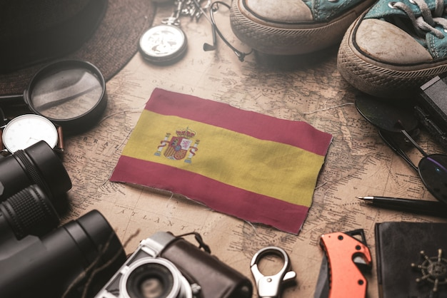 Spain flag between traveler's accessories on old vintage map. tourist destination concept.