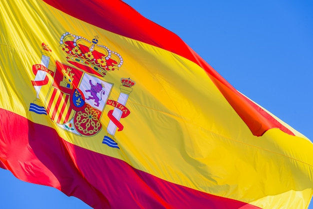 Spain flag with royal shield waving in the wind on blue sky background