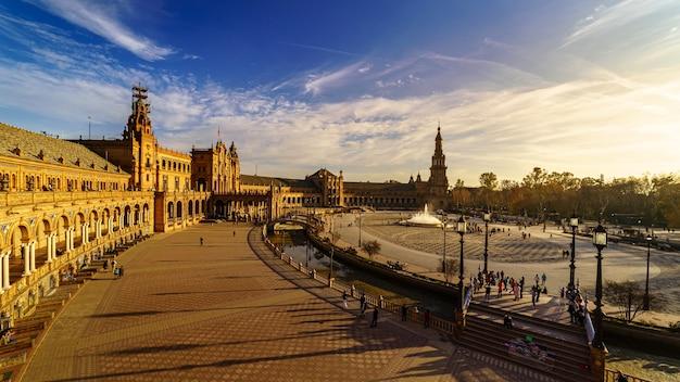 セビリアのスペイン広場、夏の日の日没で青い空と白い雲と晴れた日。ゴールデンとオレンジの色調。アンダルシア。