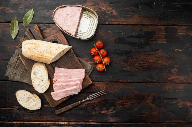 Набор бутербродов со спамом, на старом фоне темного деревянного стола, плоская планировка, вид сверху, с копией пространства для текста