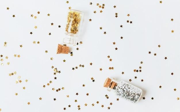 Блестки золота и серебра рассыпаны из бутылок на белом фоне