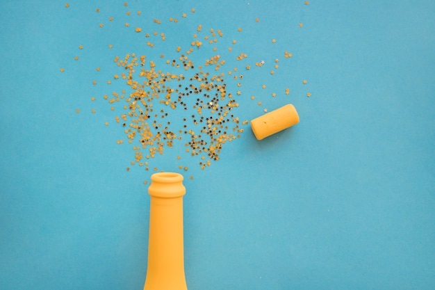 Spangles scattered from bottle on table